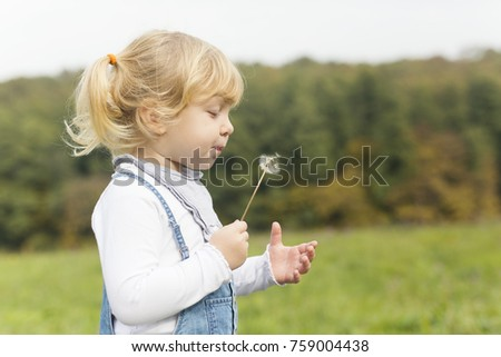 Happy little girl is playing with dandelion in the park