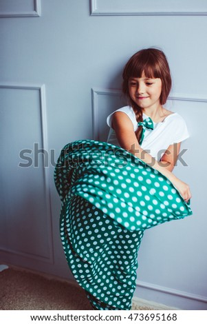 Happy little girl is playing with the skirt