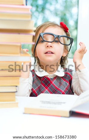 happy little girl is reading a book while wearing glasses indoors - stock photo