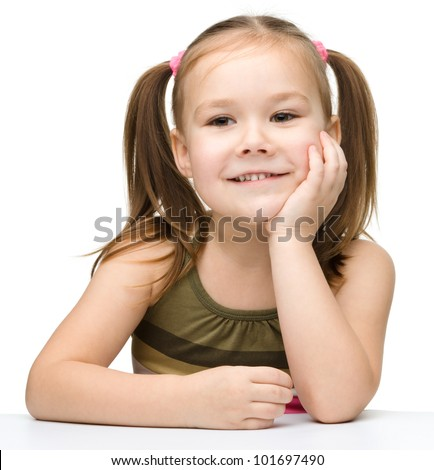 Happy little girl is sitting at a table and smile, isolated over white
