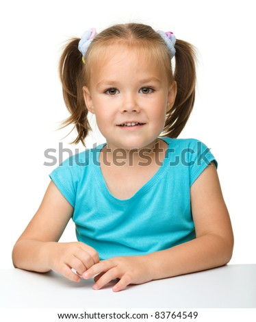 Happy little girl is sitting at the table, isolated over white - stock photo
