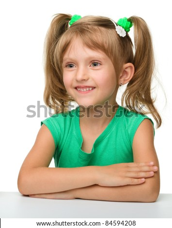 Happy little girl is sitting at the table, isolated over white