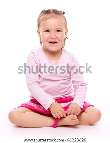 Happy little girl is sitting on floor, isolated over white