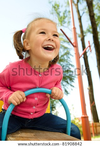 Happy little girl is swinging on see-saw - stock photo