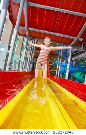 Happy little girl jumping in aquapark - stock photo