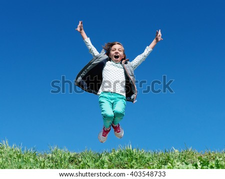 Happy little girl jumping on grass hill with blue sky