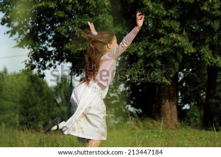 Happy little girl jumping on meadow in forest with motion blur