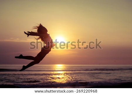 Happy little girl jumping on the beach at the sunset time