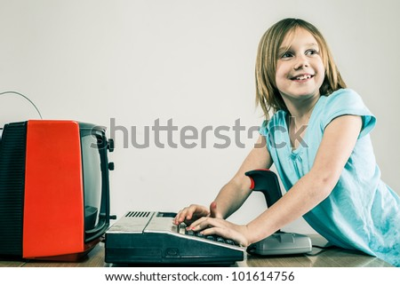 Happy little girl kid typing on vintage keypad in front of red television set and game joystick