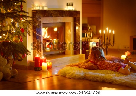 Happy little girl laying by a fireplace in a cozy dark living room on Christmas eve, unfocused - stock photo