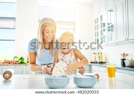 Happy little girl learning to bake with her mother standing at a kitchen counter kneading the dough for cookies