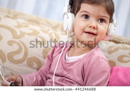 Happy little girl listening music  in the living-room - stock photo