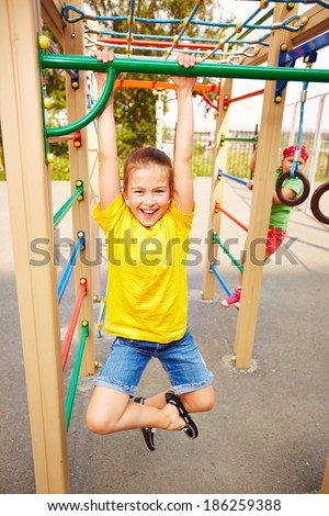 Happy little girl looking at camera on playground area - stock photo