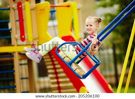 Happy little girl looking at camera while swinging on playground area - stock photo