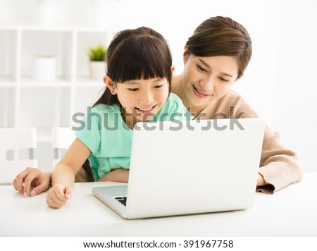 happy Little girl looking at laptop  with her mother - stock photo