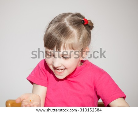 Happy little girl looking on her opened palm, grey background - stock photo