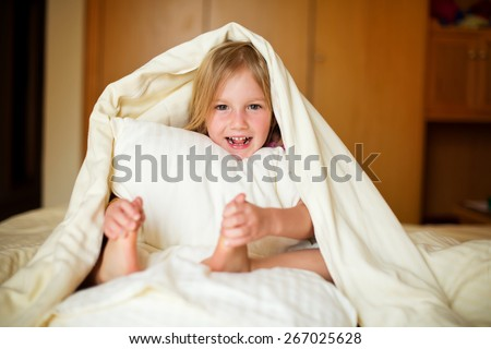 Happy little girl lying on bed under blanket and posing in room of her flat holding a pillow in hands - stock photo