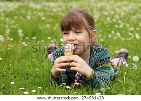 happy little girl lying on green grass and eat ice cream - stock photo