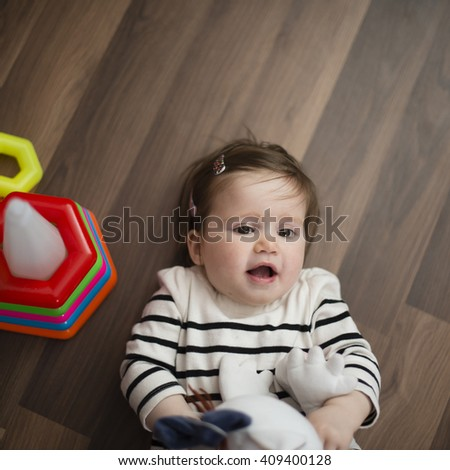 happy little girl lying on the floor and laughs - stock photo