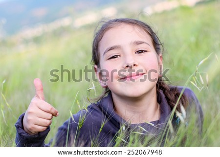 happy little girl lying on the grass showing gesture well - stock photo