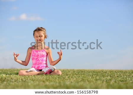 Happy little girl meditates on green field at sunny summer day. - stock photo