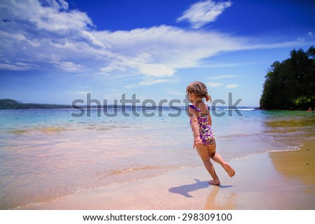 happy little girl on a beach vacation - stock photo