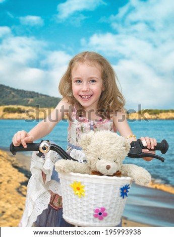 Happy little girl on a bicycle on the beach. - stock photo