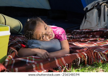 Happy little girl on a camping trip on a sunny day - stock photo