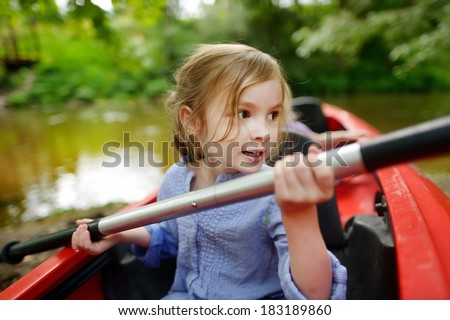 Happy little girl on a kayak on a river at summer - stock photo