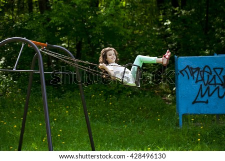 Happy Little girl on a swing in the summer park