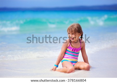 Happy little girl on a white sand beach on a beautiful ocean background