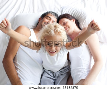Happy little girl on bed with her parents in the morning