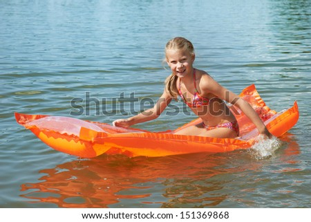 Happy little girl on mattress in lake at summer