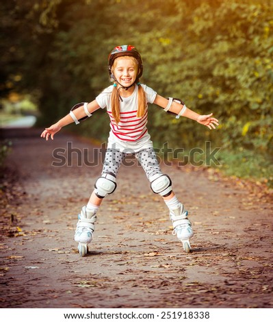 happy little girl on roller skates in the autumn forest - stock photo