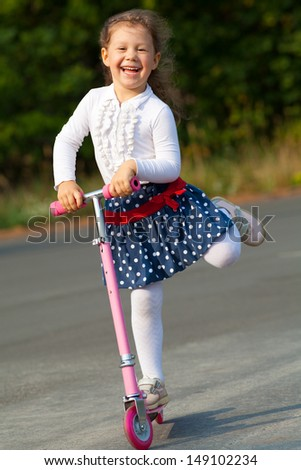 happy little girl on scooter in outdoor - stock photo
