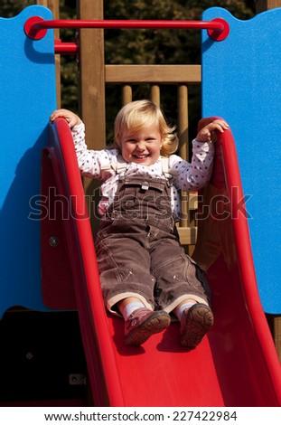 Happy little girl on slide in summer - stock photo