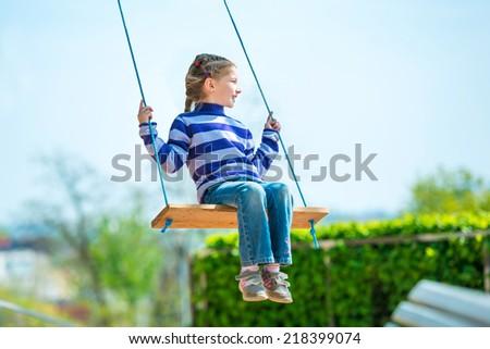 happy little girl on swing - stock photo