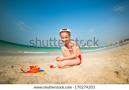 happy little girl on the beach playing in the sand