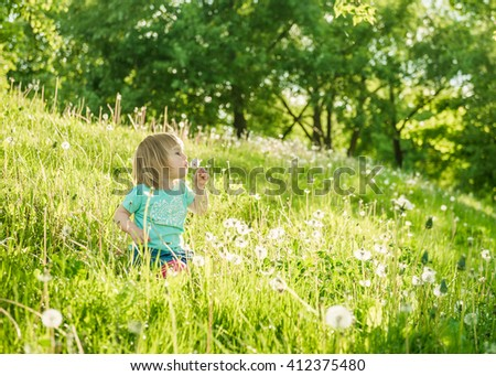 Happy little girl on the field with dandelions - stock photo