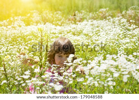Happy little girl on the flower meadow in sunny day - stock photo