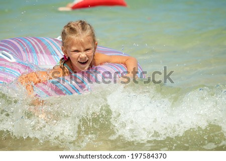 Happy little girl on the sea - stock photo