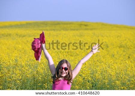 happy little girl on yellow flowers field summer season - stock photo
