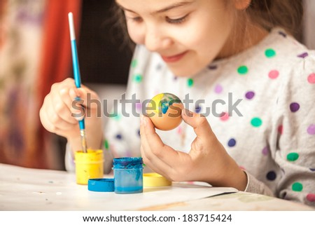 Happy little girl painting easter egg - stock photo