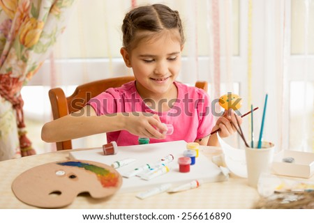 Happy little girl painting eggs for Easter - stock photo