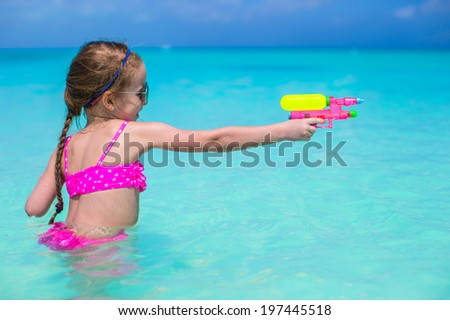 Happy little girl playing at beach during caribbean vacation - stock photo