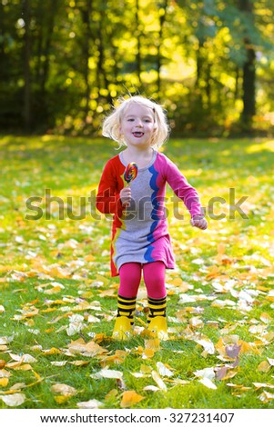 Happy little girl playing in the park on sunny autumn day. Cute funny kid eating big colorful lollipop outdoors.