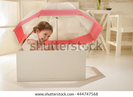 Happy little girl playing indoor sitting in white wooden box under an umbrella. Children imagination or creativity concept