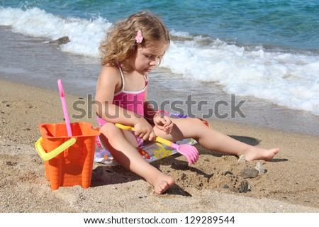 happy little girl playing on beach - stock photo