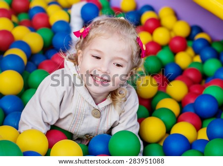 happy little girl playing on colorful balls playground - stock photo