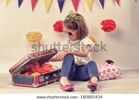 happy little girl playing with a little retro suitcase and vintage camera  - stock photo